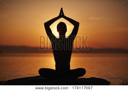 Silhouette of man sitting in lotus pose with his arms lifted above head in namaste and enjoying sunset on water background