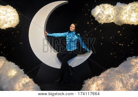 Girl in blue sitting on the moon and clouds