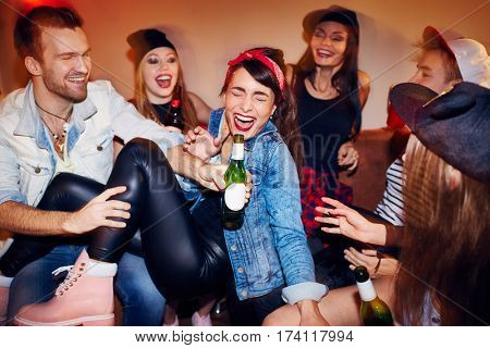 Group of trendy young people getting drunk at late night swag party, going crazy and laughing while sitting on sofa with beer bottles