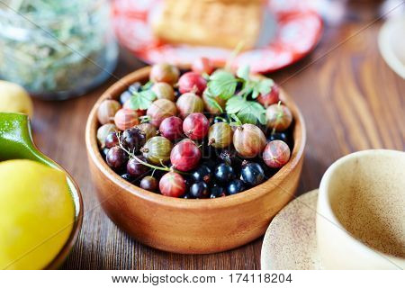 Close-up view of gooseberries and blackcurrant straight out of garden lying in round wooden bowl on table