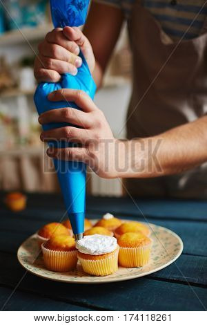 Closeup of unrecognizable man working in rustic kitchen, decorating freshly baked muffins with white cream using icing bag