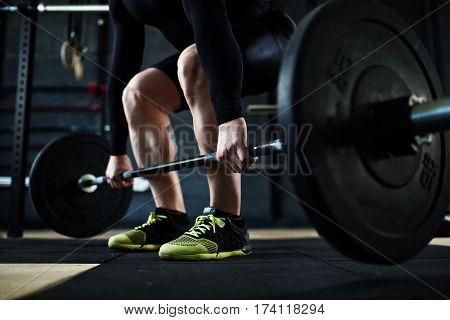 Low section of unrecognizable male athlete lifting huge heavy barbell from floor, leg muscles straining with effort