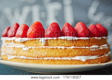 Closeup shot of simple biscuit naked cake decorated with fresh ripe strawberries on top and white icing between layers