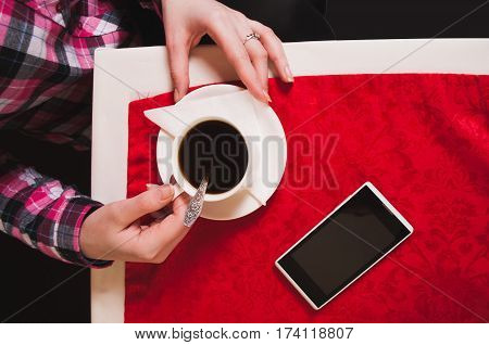 Female Hands Holding Cup Of Coffee On The Table With A Red Tablecloth,