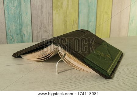 the book is on the table in a leather binding