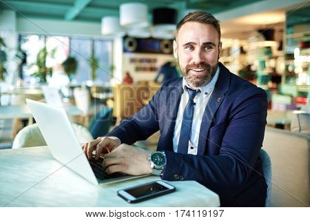 Portrait of successful mature businessman smiling and  working at laptop in modern lounge of restaurants lounge