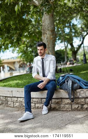 Young businessman resting at park.