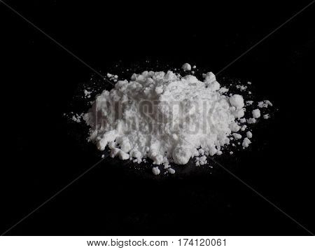 Cocaine drug powder pile on black background