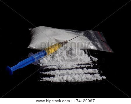 Injection syringe on cocaine drug powder bag, pile and lines
