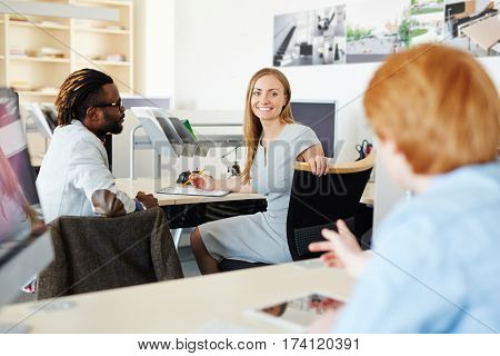 Portrait of beautiful blond-haired worker looking at camera with toothy smile while sharing ideas concerning business project with her male colleagues