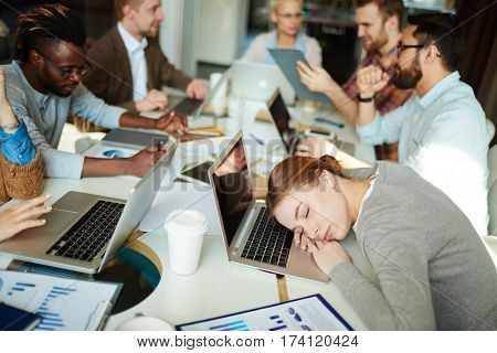 Tiresome business meeting: pretty young manager laying head on laptop and having nap while her colleagues having productive project discussion