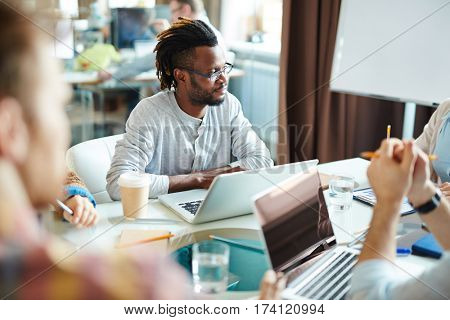 Waist-up portrait of African American employee with dreads looking at his colleague while listening to her with concentration during meeting in boardroom