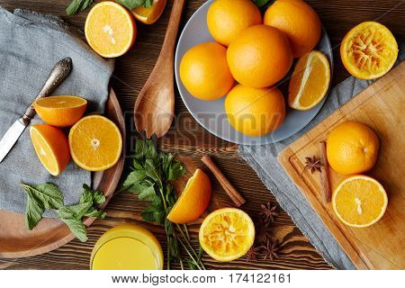 Directly above view of rustic kitchen table with homegrown fruits and spices laid out on It: delicious ripe oranges cut in half, mint, cinnamon and star anise scattered in elegant assortment