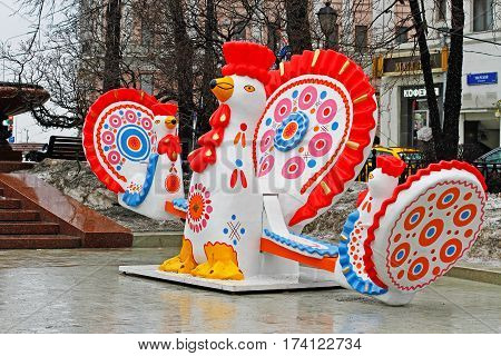 Moscow Russia - February 21 2017: Traditional Dymkovo toy Cock as art object and swing at Russian national festival