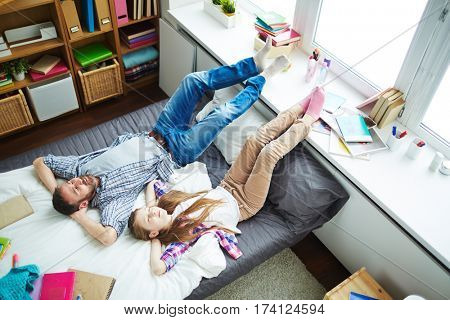 High angle view of pretty girl and her bearded father lying on bed with closed eyes and hands on nape