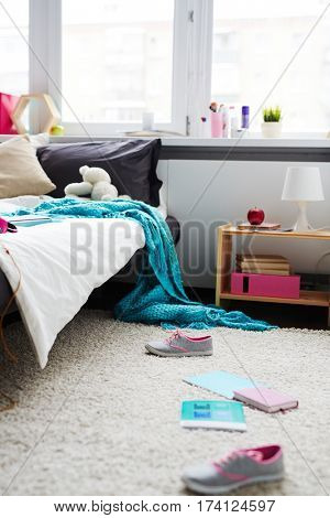Modern messy bedroom of teenage girl with sneakers, copybooks scattered on carpet and blanket hanging down from bed