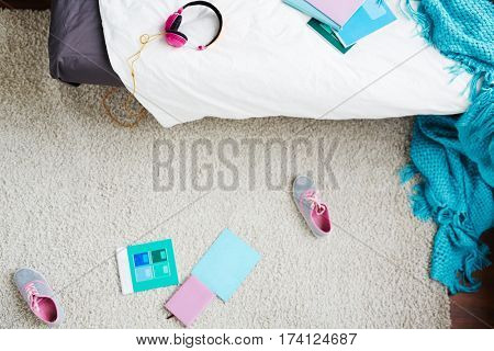Top view of school girl bedroom with unmade bed, pink headphones and scattered sneakers on carpet