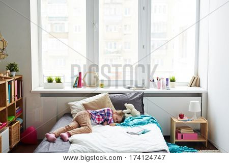 Little girl having a nap on her soft bed in bright modern room with large window