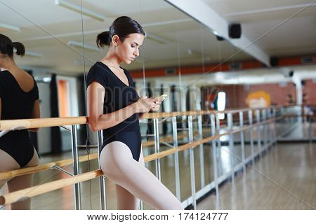 Portrait of young woman in black leotard standing leaning against bar with smartphone and typing messages at break from lesson in spacious ballet studio