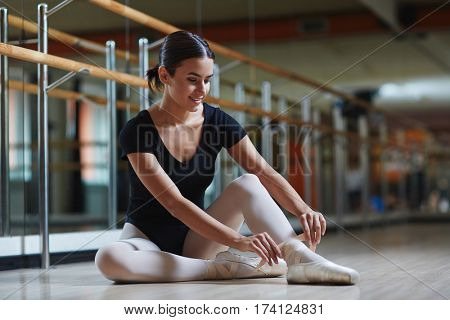Portrait of beautiful smiling Hispanic ballerina tying on pointe shoes gently preparing for ballet lesson in dance studio