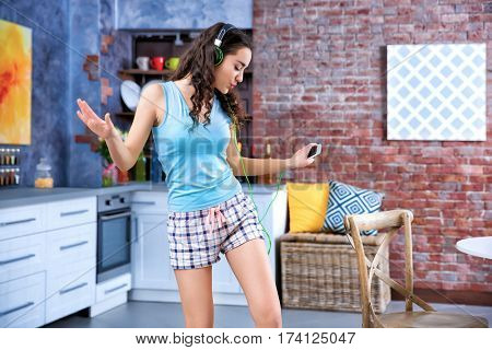 Happy young woman in headphones listening to music and dancing at home