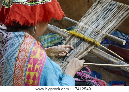 Peruvian woman in traditional clothing weaving cloth on a hand loom in the Andes Mountains. October 22, 2012 - Peru
