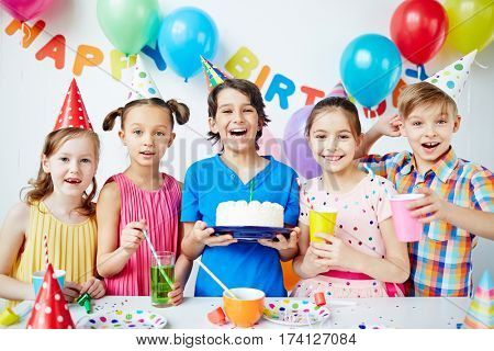 Group of agitated children together posing with birthday boy holding big birthday cake and looking at camera, all smiling cheerfully