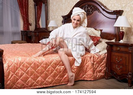 Young woman with a massager in a bedroom. Concept  of body care.
