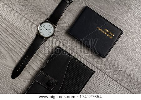 Watch with a leather strap notebook in leather cover name card holder on a gray wooden background