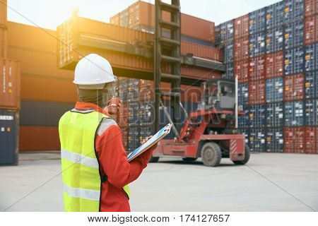 Foreman control loading Containers box from Cargo freight ship
