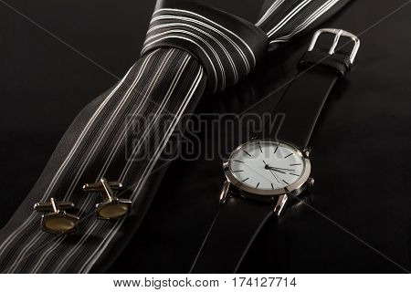 Silk tie cufflinks watch with a leather strap on a black background