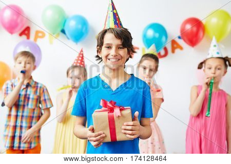Portrait of excited birthday boy holding box with present standing in front smiling happily with his friends blowing party noisemakers behind in background