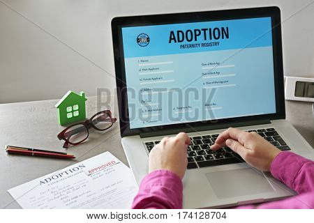 Woman filling adoption paternity registry in laptop