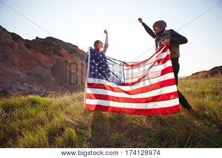 Couple of joyous young people waving big American banner jumping on top of hill in mountains