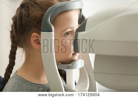 Measuring intraocular pressure of little girl in clinic, closeup