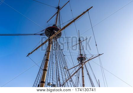 Masts, ropes and cables of an old wooden ship on the background of blue sky