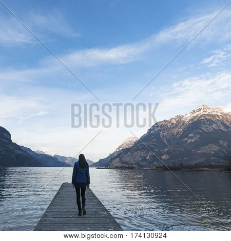 Woman goes on a wooden pier. Lake between the mountain ranges. Mountain landscape in the evening.