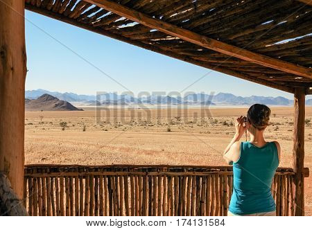 Woman tourist looking through binoculars to desert mountains, enjoying great view. Happy taking photo of open range grassland, standing under a protecting wooden shelter in a safari camp.