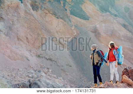 Wide shot copy space image of small figures of people in hiking gear with backpacks standing against background of enormous mountain holding hands, traveling together.