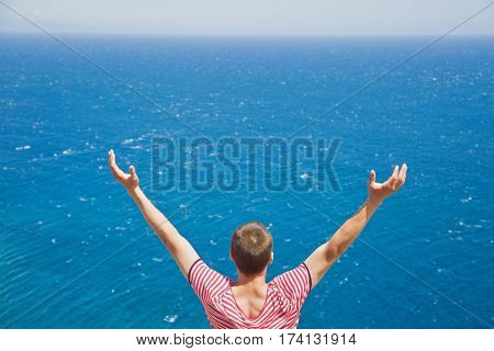 Rear view of male tourist standing with raised hands and enjoying gorgeous view of vast ocean