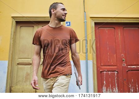 Low angle view of young bearded man in casual clothing wandering around streets of old town with his laptop after work