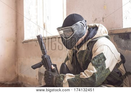 Shot of militaty man in mask with paintball weapon in his arms