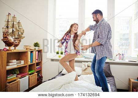 Father and his teenage daughter executing funny dance on bed covered with white and grey bedclothes, full-length portrait