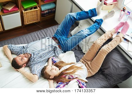 Teenage girl and her middle-aged father lying on bed with hands on nape, looking at ceiling and dreaming about future