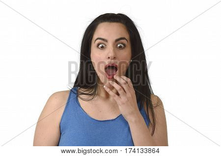 head and shoulders portrait of young beautiful hispanic woman surprised in shock and disbelief isolated on white background in emotion and opened mouth surprise face expression