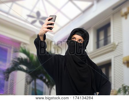technology and people concept - muslim woman in hijab taking selfie with smartphone over rich home background