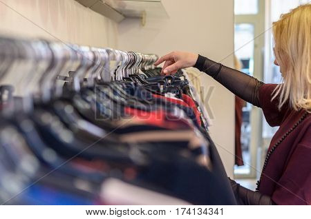 Female Shopper Searching Through Garments