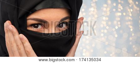 religious and people concept - close up of muslim woman in hijab over holidays lights background