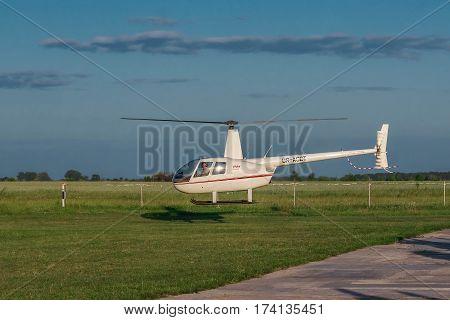 Zhitomir Ukraine - May 25 2012: Robinson R-44 light helicopter landing on sunset