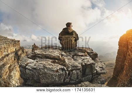 A young man sits on a rock surrounded by cliffs, located above the clouds in a great location, on a background of clouds, valleys, fields, mountains and sunset